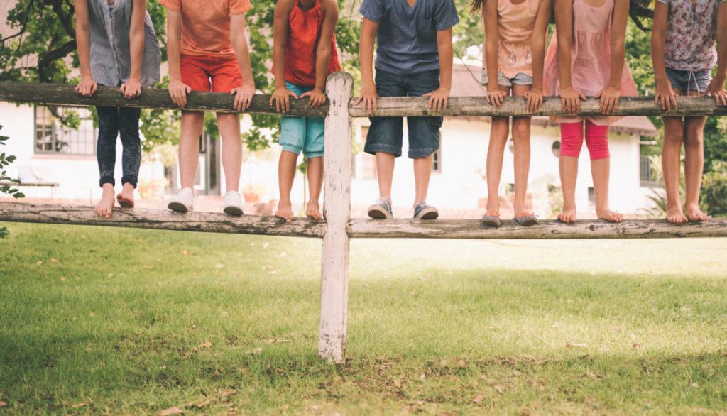 Niños en una valla de madera