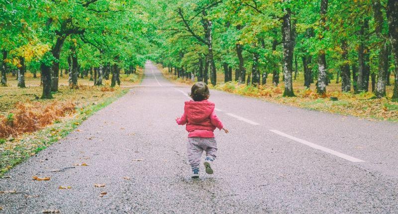 Un niño pequeño caminando por la carretera