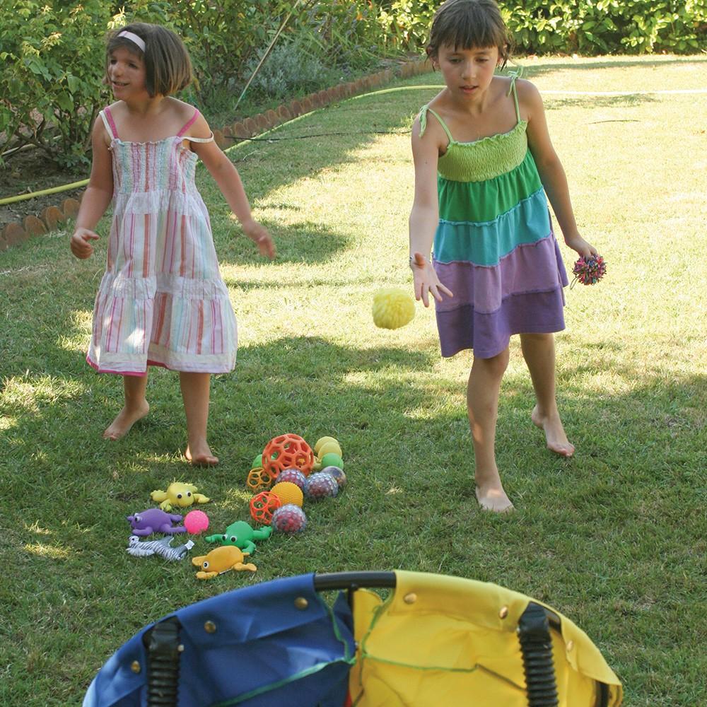 Dos niñas jugando a tirar pelotas a un blanco.