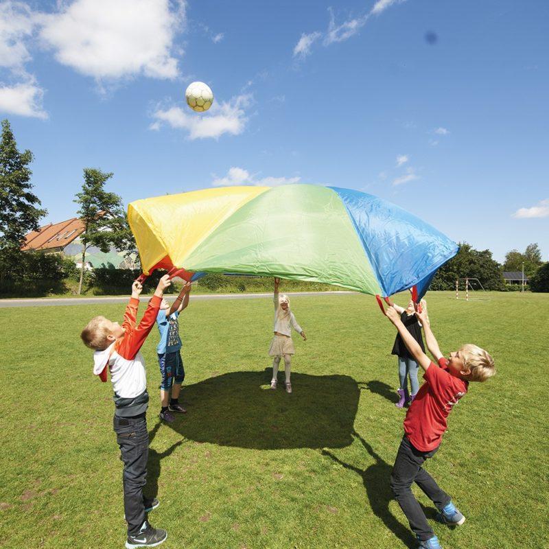 Niños jugando al juego del paracaídas.