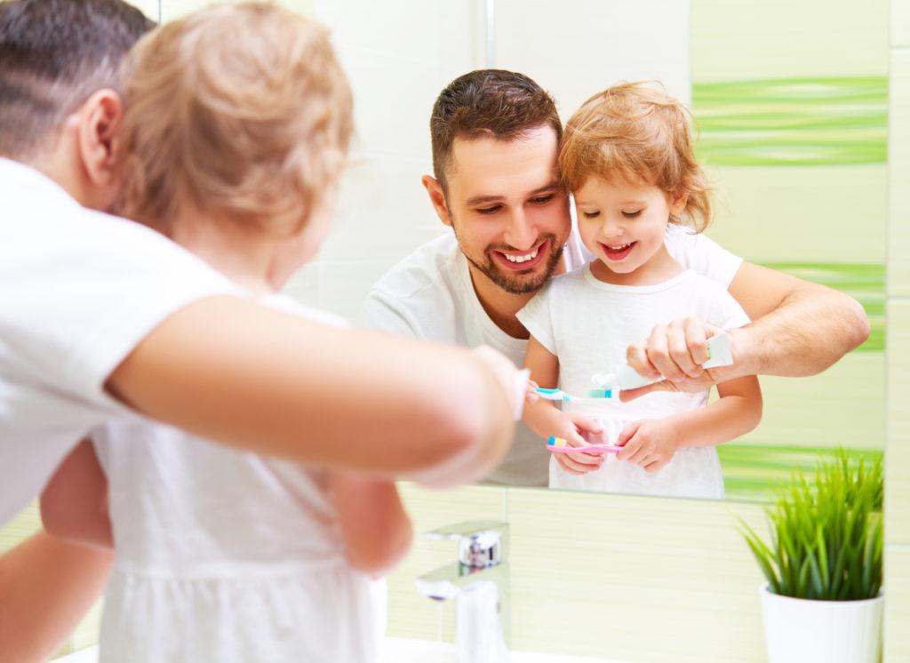 Niño cepillándose los dientes con su padre frente al espejo.