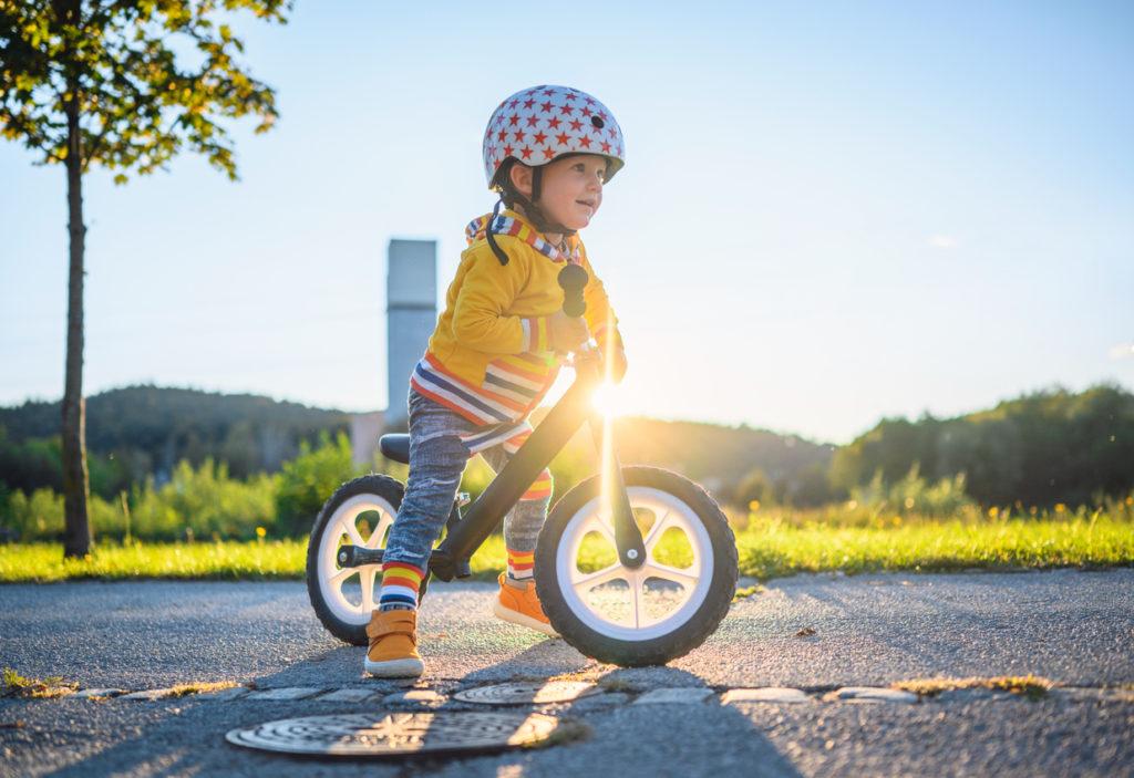Un niño aprendiendo a montar en bicicleta con una bicicleta sin pedales