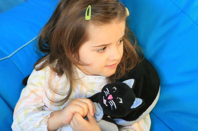 niña con gato de peluche lastrado