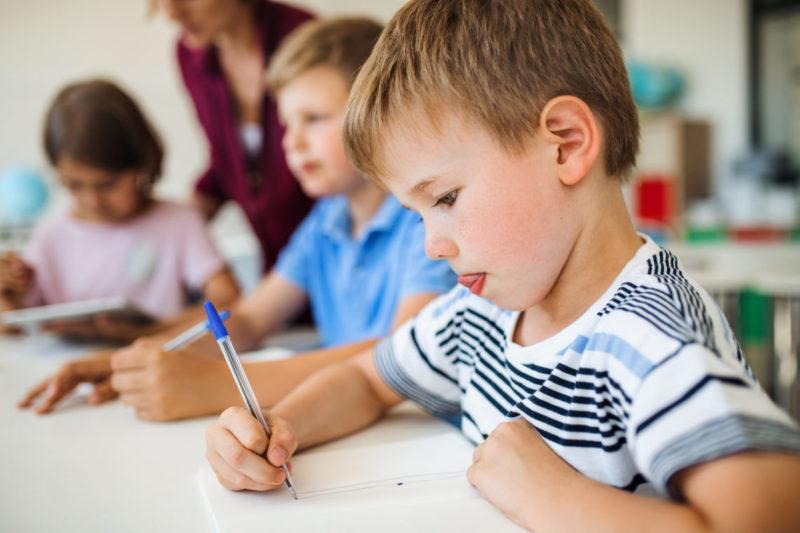 Niño concentrado aprendiendo a escribir